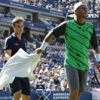 Photo - Lleyton Hewitt, of Australia, hands a towel back to a ball person after wiping sweat from his face and arms during the second round of the 2014 U.S. Open tennis tournament against Tomas Berdych, of the Czech Republic,, Wednesday, Aug. 27, 2014, in New York. (AP Photo/Elise Amendola)