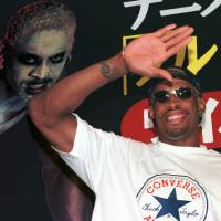 Photo - FILE - In this July 28, 1997, file photo, former NBA basketball player Dennis Rodman waves to his fans as he arrives at a Tokyo publishing house to promote his autobiography