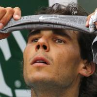 Photo - Spain's Rafael Nadal adjusts his head band during a break in the first round match of the French Open tennis tournament against Robby Ginepri of the U.S. at the Roland Garros stadium, in Paris, France, Monday, May 26, 2014. (AP Photo/Michel Spingler)