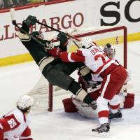 Photo - Minnesota Wild left wing Zach Parise (11) is checked hard by Detroit Red Wings defenseman Kyle Quincey (27) during the first period of an NHL hockey game, Saturday, March 22, 2014, in St. Paul, Minn. (AP Photo/Paul Battaglia)