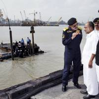 Photo - In this Wednesday, Aug. 14, 2013 photo released by the Indian Navy, Indian Defense Minister A.K. Antony, second right, listens to Navy Chief Admiral D.K. Joshi as navy personnel inspect a Russian-made submarine, INS Sindhurakshak, at a naval dockyard where it caught fire and sank after twin explosions, in Mumbai, India. Indian navy divers on Friday recovered three severely burned bodies of sailors who had been trapped inside a submarine damaged by twin explosions, a navy spokesman said. He added that it was doubtful that any of the other 15 sailors aboard survived. (AP Photo/Indian Navy)