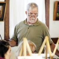 "Photo - Artist Rick Fry checks on the progress of participants in the ""Corkscrews and Canvas"" painting party."