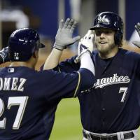 Photo - Milwaukee Brewers' Mark Reynolds (7) is greeted at home plate by teammate Carlos Gomez (27) after Reynolds hit a two-run home run against the Miami Marlins in the fifth inning of a baseball game in Miami, Friday, May 23, 2014. Gomez scored on the home run. (AP Photo/Alan Diaz)
