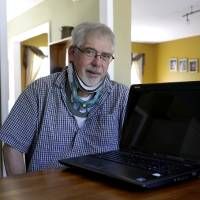 Photo - This photo taken May 8, 2014 shows Mark Matulaitis posing with his laptop that he uses for virtual house calls with his neurologist in his home in Salisbury, Md. Matulaitis has had Parkinson's disease since 2011 and sees a neurologist at the University of Rochester via his laptop and special Skype-like software.  (AP Photo/Patrick Semansky)