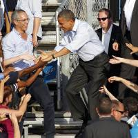 Photo -   President Barack Obama is greeted by supporters during a campaign event at McArthur High School in Hollywood, Fla., Sunday, Nov. 4, 2012. (AP Photo/Terry Renna)
