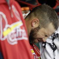 Photo - FILE - In this Oct. 21, 2012, file photo, St. Louis Cardinals' Chris Carpenter wipes his face with a towel in the dugout during the fourth inning of Game 6 of baseball's National League championship series against the San Francisco Giants in San Francisco. Carpenter is unlikely to pitch for the Cardinals this season and his career may be over because of a nerve injury that kept him out most of last year, general manager John Mozeliak said Tuesday, Feb. 5, 2013. (AP Photo/David J. Phillip, File)