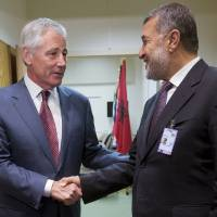 Photo - U.S. Defense Secretary Chuck Hagel, left, shakes hands with Afghanistan's Defense Minister Bismillah Khan Mohammadi, right, ahead of their North Atlantic Council (NAT) meeting, in Brussels, Wednesday, June 4, 2014. (AP Photo/Pablo Martinez Monsivais, Pool)