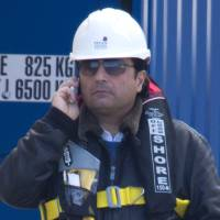 Photo - Captain Francesco Schettino talks on the phone as he waits to board the wreck of the Costa Concordia cruise ship, just off the coast of the Giglio island, Thursday, Feb. 27, 2014. The captain of the Costa Concordia has been permitted to go aboard the shipwreck for the first time since it capsized two years ago as part of a new court-ordered search. Consumer groups and lawyers for Capt. Francesco Schettino asked the court in Grosseto to authorize the searches to determine if any factors beyond human error contributed to the disaster. After searching the bridge and elevators last month, experts will examine the emergency generators Thursday. (AP Photo/Andrew Medichini)