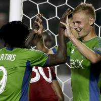 Photo - Seattle Sounders midfielder Andy Rose, right, celebrates his second goal with forward Obafemi Martins during the first half of an MLS soccer match against Chivas USA on Wednesday, Sept. 3, 2014, in Carson, Calif. (AP Photo/Chris Carlson)