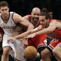 Photo - Brooklyn Nets center Brook Lopez (11), Chicago Bulls forward Carlos Boozer, center, and center Joakim Noah, right, compete for a loose ball in the first half of Game 5 of their first-round NBA basketball playoff series, Monday, April 29, 2013, in New York. (AP Photo/Kathy Willens)