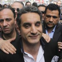 Photo - A bodyguard secures  popular Egyptian television satirist Bassem Youssef, who has come to be known as Egypt's Jon Stewart, as he enters Egypt's state prosecutors office to face accusations of insulting Islam and the country's Islamist leader in Cairo, Egypt, Sunday, March 31, 2013. Government opponents said the warrant against such a high profile figure, known for lampooning President Mohammed Morsi and the new Islamist political class, was an escalation in a campaign to intimidate critics. (AP Photo/Amr Nabil)