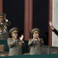 Photo - FILE - In this Saturday April 14, 2012 file photo, North Korean leader Kim Jong Un, left, waves as North Korean military officers clap at a stadium in Pyongyang during a mass meeting called by the Central Committee of North Korea's ruling party. Kang Dong-wan, a cross-border relations expert at Dong-A University in Busan, believes South Koreans should start taking North Korean threats more seriously than before because Pyongyang's young leader, Kim Jong Un, is still tightening his grip on power and has not been proven to make sound military judgments. (AP Photo/Ng Han Guan, File)