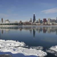 Photo - Ice floats on the surface of Lake Michigan Friday, Jan. 3, 2014, in Chicago. Single-digit temperatures are hitting Illinois after the state was blanketed in snow. Meanwhile, residents are bracing for a deep freeze. Highs early next week likely won't reach zero and wind chills could sink to 45 below. (AP Photo/M. Spencer Green)