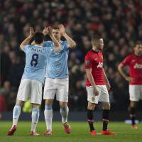Photo - Manchester City's Edin Dzeko, second left, celebrates with teammates Samir Nasri after scoring against Manchester United during their English Premier League soccer match at Old Trafford Stadium, Manchester, England, Tuesday March 25, 2014. (AP Photo/Jon Super)