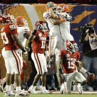Photo - Florida's Louis Murphy, left, and Riley Cooper celebrate a touchdown behind OU's Lendy Holmes and Dominique Franks during the first half of the BCS National Championship game. Photo by Bryan Terry.