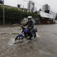 Photo - Motorcyclists make their way down a flooded street after heavy rain storms in Recife, Brazil, Thursday, June 26, 2014. The World Cup soccer match between the USA and Germany will be played at the Arena Pernambuco in Recife today.  (AP Photo/Petr David Josek)