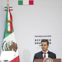 Photo - Mexico's President Enrique Pena Nieto pauses during a speech at the National Palace where he signed into law a plan to overhaul his country's public education system, in Mexico City, Monday, Feb. 25, 2013. The law which was approved by Congress in December, calls for creation of a professional system for hiring, evaluating and promoting teachers without the