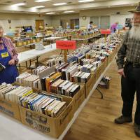 Photo -  Sales managers Lori and Simm Rudnick supervise volunteers as they get ready for the Friends of the Norman Library's Better Books Sale that opens Friday and continues through Sunday. PHOTO BY STEVE SISNEY, THE OKLAHOMAN   STEVE SISNEY