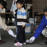 Photo - FILE - In this April 16, 2011 file photo, Wakana Nemoto, 3, standing next to her mother Naoko, receives a radiation exposure screening outside an evacuation center in Fukushima, northeastern Japan. People exposed to the highest doses of radiation during the Fukushima nuclear plant disaster in 2011 may have a slightly higher risk of cancer that is so small it probably won't even be detectable, according to a new report from the World Health Organization released on Thursday Feb. 28, 2013. (AP Photo/Hiro Komae, File)