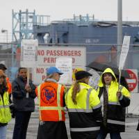 Photo - Clerical workers picket in the rain at entrance to Pier 400 at the Port of Los Angeles Thursday, Nov. 29, 2012.  Cargo ships were stacking up at the ports of Los Angeles and Long Beach as a strike by about about 70 clerical workers shut down most of the terminals that together are the nation's busiest port complex.  Dockworkers were refusing to cross the picket lines even though an arbitrator ruled the walkout invalid on Tuesday.  By Thursday morning, at least 18 ships docked and inside the adjacent harbors were not being serviced, port spokesmen said. (AP Photo/Nick Ut)
