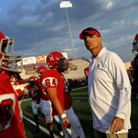 Photo - Carl Albert assistant coach Mike Corley talks with Carl Albert players before a high school football game between Carl Albert and Coweta in Midwest City, Friday, September 7, 2012.