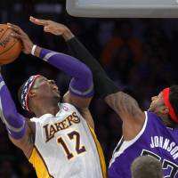 Photo -   Los Angeles Lakers center Dwight Howard, left, puts up a shot as Sacramento Kings forward James Johnson defends during the first half of their NBA basketball game, Sunday, Nov. 11, 2012, in Los Angeles. (AP Photo/Mark J. Terrill)