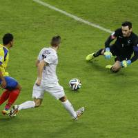 Photo - Ecuador's Jefferson Montero, left, takes a shot which is saved by France's goalkeeper Hugo Lloris as France's Lucas Digne, center, moves in during the group E World Cup soccer match between Ecuador and France at the Maracana Stadium in Rio de Janeiro, Brazil, Wednesday, June 25, 2014. (AP Photo/Andrew Medichini)