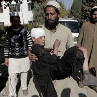 Photo - FILE - In this file photo taken Thursday, Nov. 28, 2013, an Afghan man carries an injured boy to a hospital after two roadside bombs struck the Achin district of Jalalabad, east of Kabul, Afghanistan. The number of children killed and wounded in Afghanistan's war jumped by 34 percent in 2013 as the Taliban intensified armed attacks across the country and continued to lay thousands of roadside bombs, according to a U.N. report Saturday, Feb. 8, 2014. (AP Photo/Rahmat Gul, File)