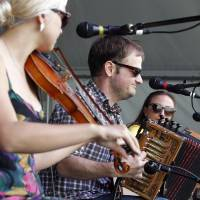 Photo - The Cajun band T'Monde performs on the Fais Do Do stage during the New Orleans Jazz and Heritage Festival in New Orleans, Friday, April 26, 2013. From left are band members Kelli Jones-Savoy playing fiddle, Drew Simon on the accordion, and Megan Brown on guitar. (AP Photo/Doug Parker)