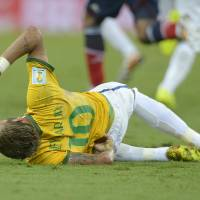 Photo - Brazil's Neymar holds his back after being fouled during the World Cup quarterfinal soccer match between Brazil and Colombia at the Arena Castelao in Fortaleza, Brazil, Friday, July 4, 2014. (AP Photo/Manu Fernandez)