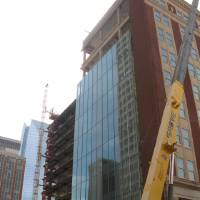 Photo - A modern glass facade is going up on the east alley side of the Braniff Building as renovations continue as part of the SandRidge Commons.  Steve Lackmeyer