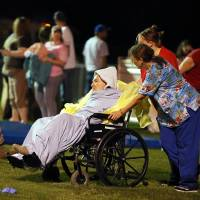 Photo - Emergency workers assist an elderly person at a staging area at a local school stadium Wednesday, April 17, 2013, in West, Texas. An explosion Wednesday night at a fertilizer plant near Waco sent flames shooting high into the night sky, leaving the factory a smoldering ruin, causing major damage at nearby buildings and injuring numerous people. (AP Photo/Waco Tribune Herald, Rod Aydelotte)