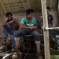 Photo - In this June 19, 2014 photo, young Central American migrants traveling together play cards on a parked boxcar as they wait for a northbound freight train at the station in Arriaga, Chiapas state, Mexico. United Nations officials are pushing for many of the Central Americans fleeing to the U.S. to be treated as refugees displaced by armed conflict, a designation meant to increase pressure on the United States to accept tens of thousands of people currently ineligible for asylum. (AP Photo/Rebecca Blackwell)