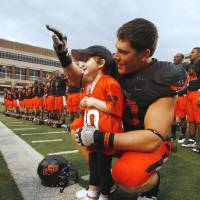 Photo - Taylor Brandt and Cooper Bassett sing the OSU alma mater and wave at fans after last season's win over Kansas. The big football player and the tiny first-grader seem an unlikely pair, but their personalities are a perfect match.  PHOTO BY STEVE SISNEY, The Oklahoman Archives