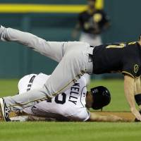 Photo - Pittsburgh Pirates second baseman Jayson Nix falls over Detroit Tigers' Don Kelly after throwing to first for the out on Tigers' runner Nick Castellanos during the seventh inning of an interleague baseball game, Wednesday, Aug. 13, 2014 in Detroit. (AP Photo/Carlos Osorio)