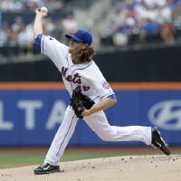 Photo - New York Mets starting pitcher Jacob deGrom throws during the first inning of the baseball game against the Miami Marlins, Sunday, July 13, 2014 in New York. (AP Photo/Seth Wenig)