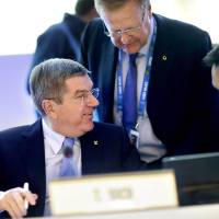 Photo - International Olympic Committee President Thomas Bach, left, talks with Director General Christophe De Kepper, right, and executive board member John Coates, prior to opening the IOC's general assembly at the 2014 Winter Olympics, Wednesday, Feb. 5, 2014, in Sochi, Russia. (AP Photo/David Goldman)