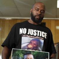 Photo - Michael Brown Sr., holds up a photo of himself, his son, Michael Brown, and a young child during a news conference Monday, Aug. 11, 2014, in Jennings, Mo. Michael Brown, 18, was shot and killed in a confrontation with police in the St. Louis suburb of Ferguson, Mo, on Saturday, Aug. 9, 2014.(AP Photo/Jeff Roberson)