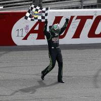 Photo - Kyle Busch (18) celebrates with the checkered flag after winning the NASCAR Sprint Series auto race in Fontana, Calif., Sunday, March 23, 2014. (AP Photo/Alex Gallardo)