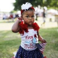 Photo -  Makinzee Sigler wears red, white and blue and carries a flag at last year's Norman Day celebration in Reaves Park. PHOTO BY K.T. KING, THE OKLAHOMAN ARCHIVES    KT King -