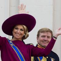 Photo - FILE - In his Sept. 18, 1012 file photo Princess Maxima, left, and Crown Prince Willem Alexander, wave to well wishers from the balcony of Royal Palace Noordeinde in The Hague, Netherlands. Prince Willem-Alexander's ascension to the Dutch throne in April 2013 promises to be a shining moment on the world stage for his wife Maxima and her home country of Argentina. But there will be a glaring absence at the ceremony. Queen Beatrix's announcement this week that she'll step aside and let her son become king raised new questions about the future queen's father, Jorge Zorreguieta, one of the longest-serving civilian ministers in Argentina's 1976-1983 military dictatorship.(AP Photo/Vincent Jannink, file)