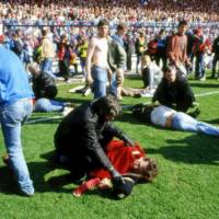 Photo - FILE- In this file photo dated April 15, 1989, police, stewards and supporters care for supporters on the field after many fans were crushed onto the barriers at Hillsborough Football Stadium, in Sheffield, England, on April 15, 1989,  when fans surged forward during the Cup semi-final between Liverpool and Nottingham Forest at Hillsborough Stadium killing 96 people. After years of campaigning to expose alleged wrongdoing by the authorities, new inquests into Britain's worst sports disaster are beginning Monday March 31, 2014, with the families of the 96 Liverpool fans crushed to death at Hillsborough seeking verdicts of unlawful killing. (AP Photo, FILE)