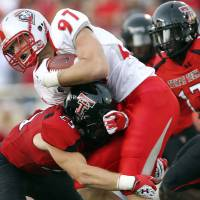 Photo - New Mexico's Lucas Reed is tackled by Texas Tech's Blake Dees (25) and Sam Eguavoen (13) during their NCAA college football game in Lubbock, Texas, Saturday, Sept. 15, 2012. (AP Photo/The Avalanche-Journal, Stephen Spillman) ALL LOCAL TV OUT ORG XMIT: TXLUB102