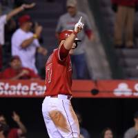 Photo - Los Angeles Angels' Mike Trout point to first base after scoring on a hit by Howie Kendrick during the ninth inning of a baseball game against the Oakland Athletics, Wednesday, April 16, 2014, in Anaheim, Calif. (AP Photo/Mark J. Terrill)