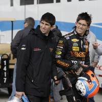 Photo - Brothers Ricky Taylor, left, and Jordan Taylor walk through the garage area after a practice session for the IMSA Series Rolex 24 hour auto race at Daytona International Speedway in Daytona Beach, Fla., Thursday, Jan. 23, 2014.(AP Photo/John Raoux)