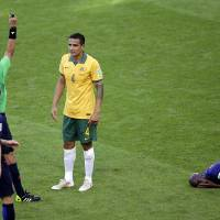 Photo - Australia's Tim Cahill, center, is booked by referee Djamel Haimoudi from Algeria, left, after tackling Netherlands' Bruno Martins Indi during the group B World Cup soccer match between Australia and the Netherlands at the Estadio Beira-Rio in Porto Alegre, Brazil, Wednesday, June 18, 2014.  (AP Photo/Michael Sohn)