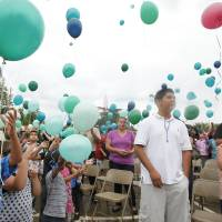 Photo - Kierra Martinez, lower left releases a balloon May 11 during a memorial for Eugene Field Elementary School kindergarten student Evelyn De Los Santos, in Oklahoma City. Photos By Steve Gooch, The Oklahoman