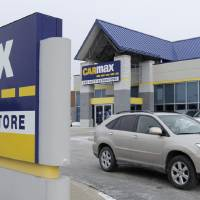 Photo - FILE - In this file photo taken Monday, Dec. 20, 2010, a car drives past the CarMax sign at the dealership in Oak Lawn, Ill. CarMax on Monday, April 28, 2014 said it is ending its sponsorship of the NBA's Los Angeles Clippers in the wake of racist comments attributed to team owner Donald Sterling. (AP Photo/M Spencer Green, File)