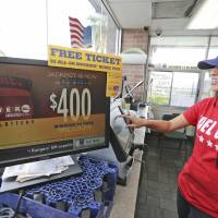 Photo - Karen Morales prints out a Powerball lottery ticket for sale to a customer at the Fuel City in Dallas on Wednesday, Sept. 18, 2013. For Wednesday's drawing, Powerball's estimated $400 million jackpot will be the nation's fifth-largest ever. (AP Photo/LM Otero)