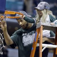 Photo - Michigan State forward Adreian Payne, left, cuts the net with Lacey Holsworth, who is battling cancer and has become close to Payne, after Michigan State defeated Michigan 69-55 in an NCAA college basketball game in the championship of the Big Ten Conference tournament on Sunday, March 16, 2014, in Indianapolis. (AP Photo/Michael Conroy)